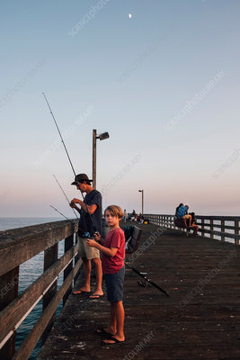 Father and son on pier fishing, USA