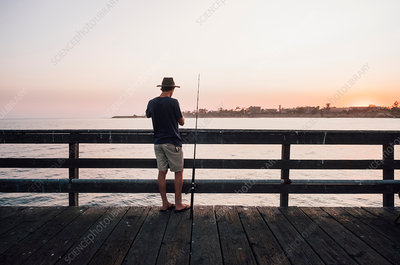 Rear view of man on pier fishing, USA