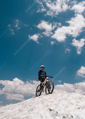Man with bike on top of snow covered hill, California, USA
