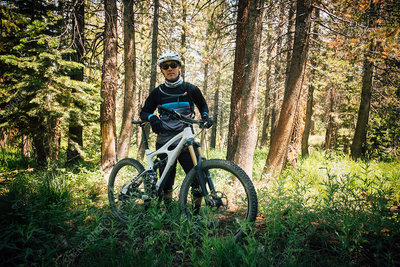 Man in forest with mountain bike, looking at camera, USA