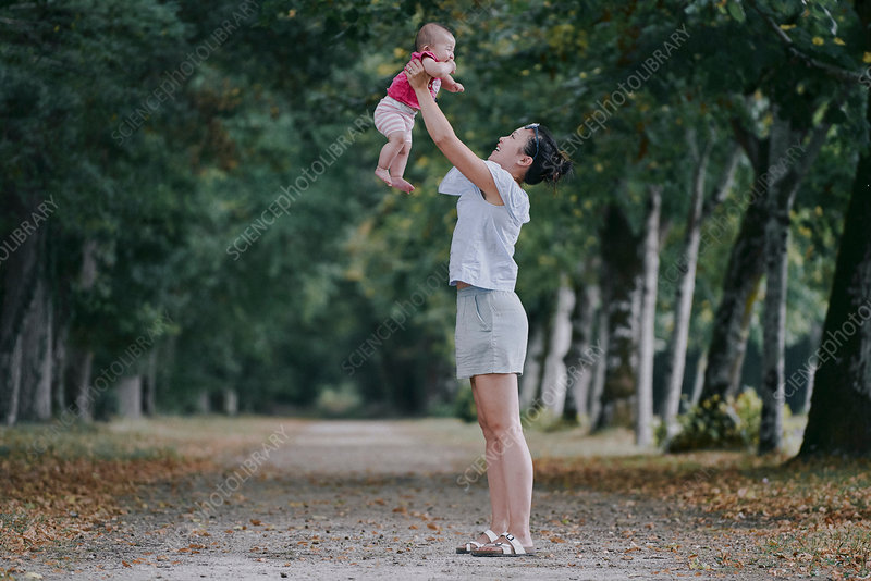 Woman holding up baby daughter in tree lined park, France