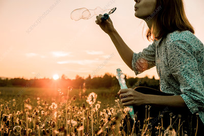 Woman blowing bubbles at sunset, Ural, Sverdlovsk, Russia