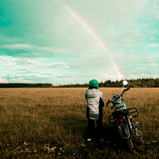 Boy by motorbike looking at rainbow, Russia