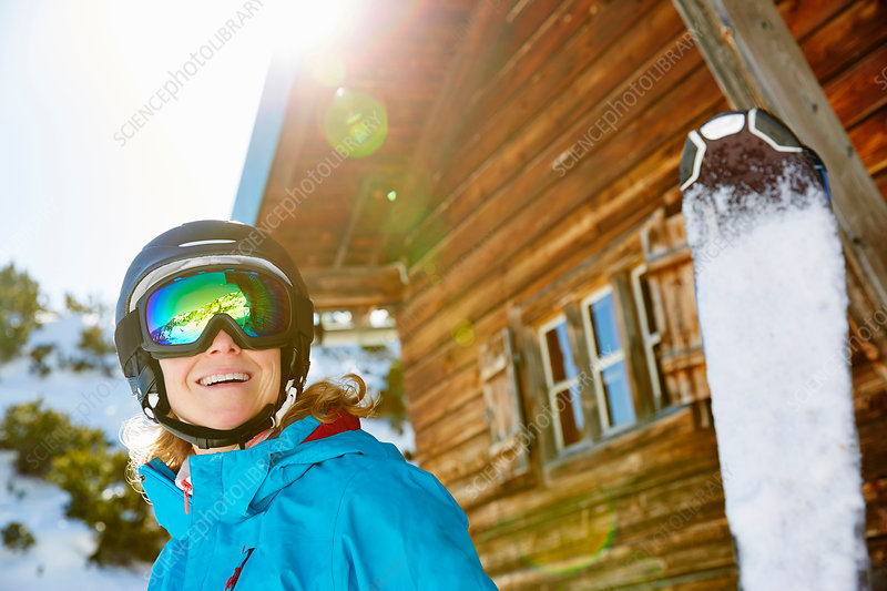Portrait of woman in front of ski lodge, holding skis