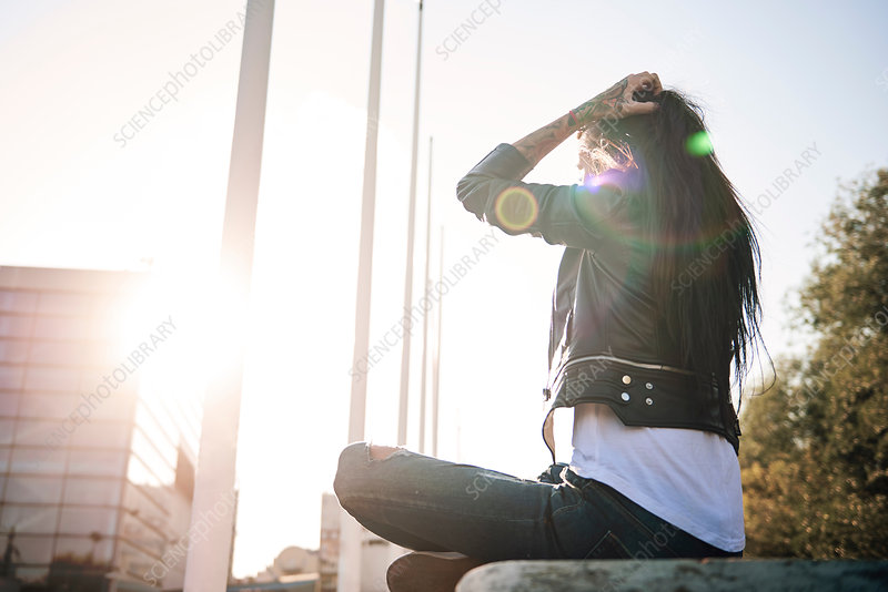 Young woman sitting cross-legged on wall, facing sunlight