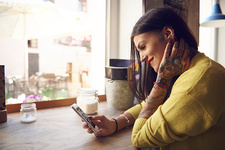 Young woman sitting in cafe, using smartphone