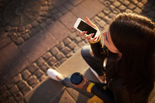 Young woman sitting outdoors, using smartphone