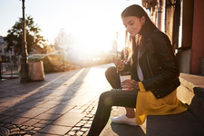Young woman outdoors, holding coffee cup and smartphone