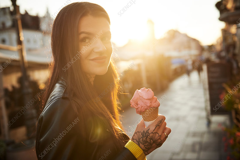Portrait of young woman holding ice cream, tattoos on hand