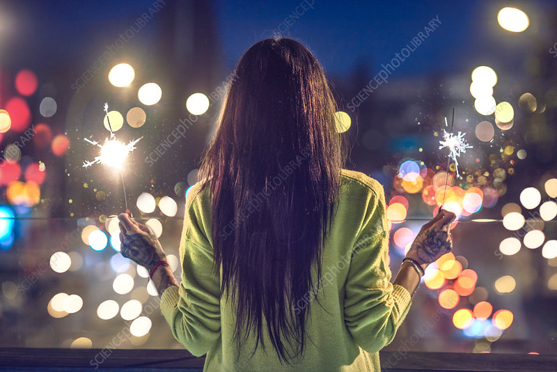 Young woman outdoors at night, holding lit sparklers