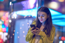 Young woman outdoors at night, using smartphone and neck
