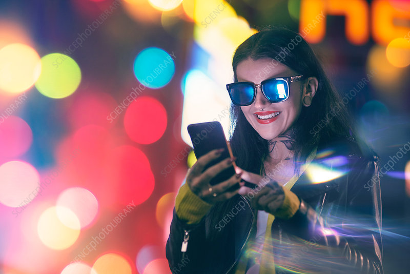 Young woman, outdoors at night, using smartphone, smiling