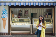 Young woman, outside ice cream parlour, using smartphone