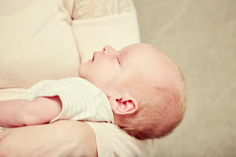 Newborn baby boy, sleeping in mother's arms, close-up