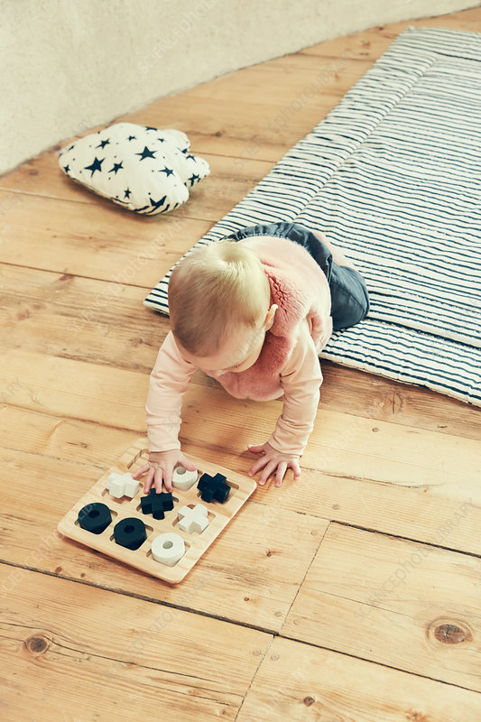 Baby girl playing with noughts and crosses on floorboards