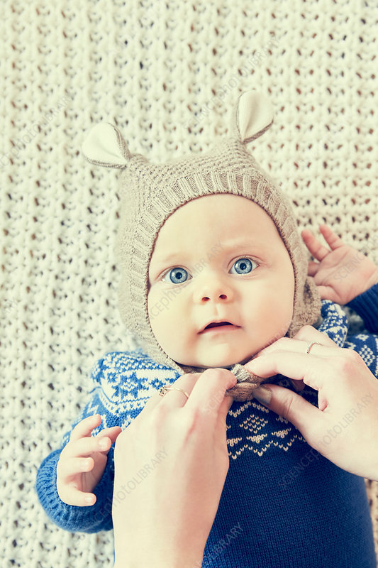 Mother's hands fastening baby son's knitted hat with ears