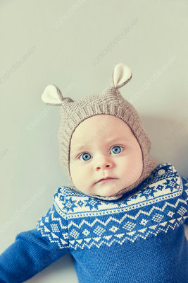 Portrait of blue eyed baby boy in knitted hat with ears