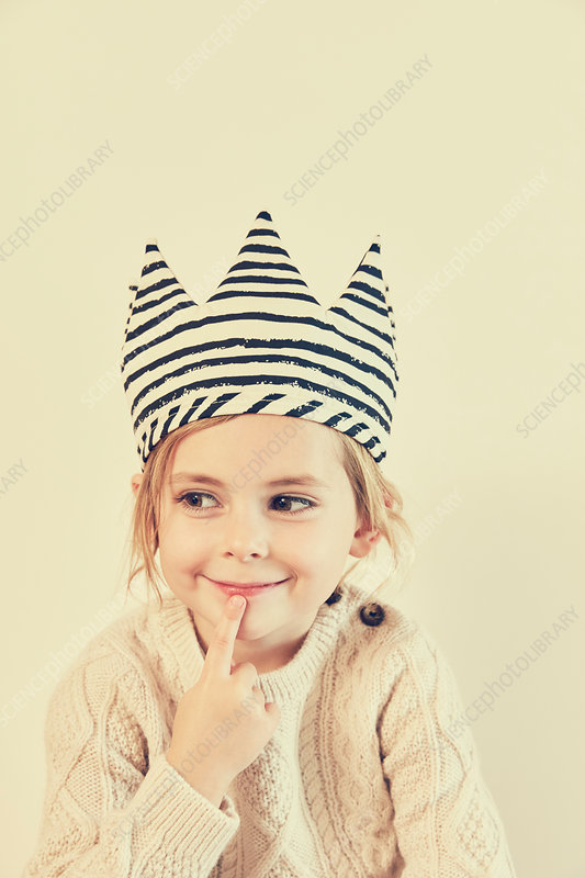 Portrait of girl in striped crown with finger on her lips