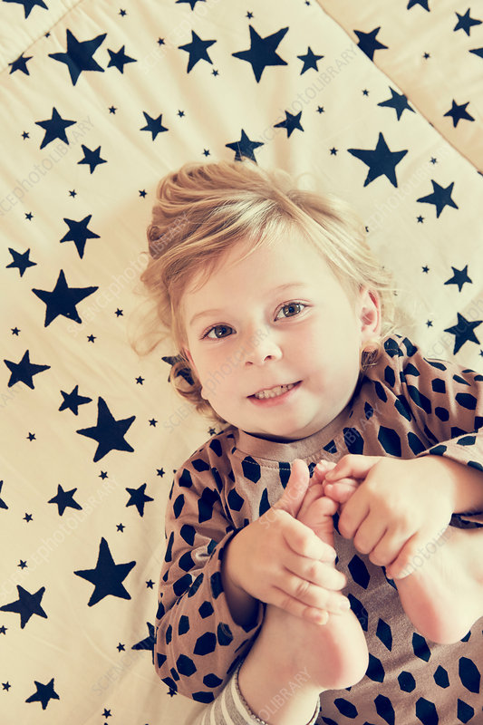Portrait of female toddler lying on star pattern bed