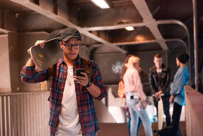 Young male skateboarder looking at smartphone