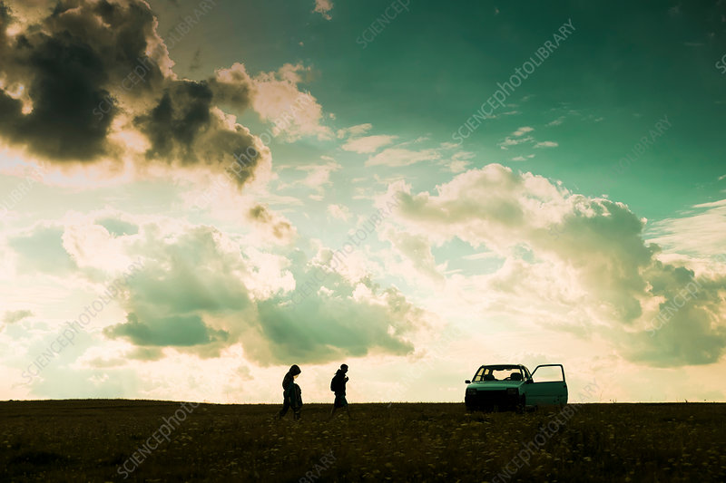 Father and son walking across field, towards car, Russia
