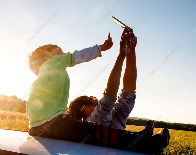 Father and son in rural setting, taking selfie, Russia