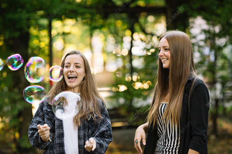 Two young female friends bursting floating bubbles in park