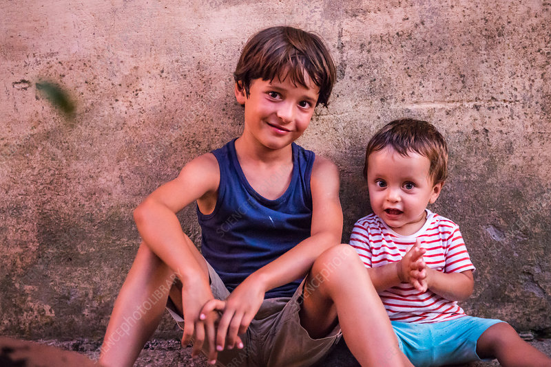 Portrait of boy and toddler brother sitting against wall