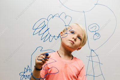 Boy admiring his marker pen drawing on glass wall