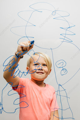 Boy drawing with marker pen onto glass wall