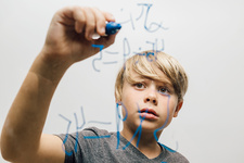 Close up of boy's hand writing equation onto glass wall