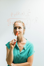 Young woman gazing at complex equation on glass wall