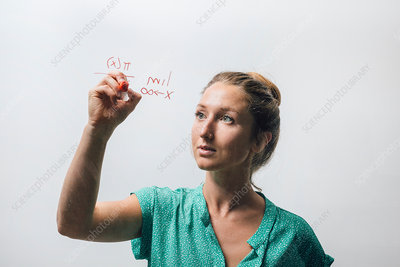 Young woman writing complex equation onto glass wall