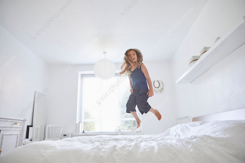 Young girl jumping on bed, low angle view