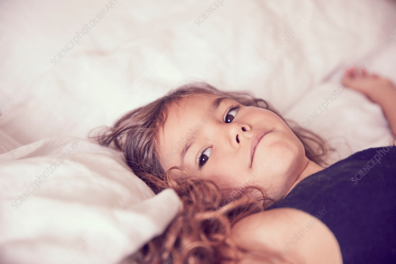Young girl lying on bed, pensive expressions