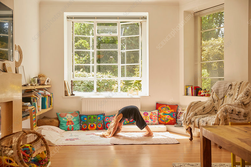 Young girl at home, bent over in yoga position