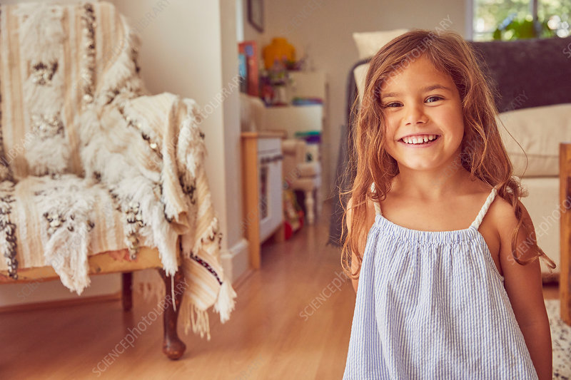 Portrait of young girl at home, smiling