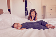 Female toddler, sleeping on bed with older sister