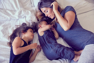 Mother and two young children, lying on bed