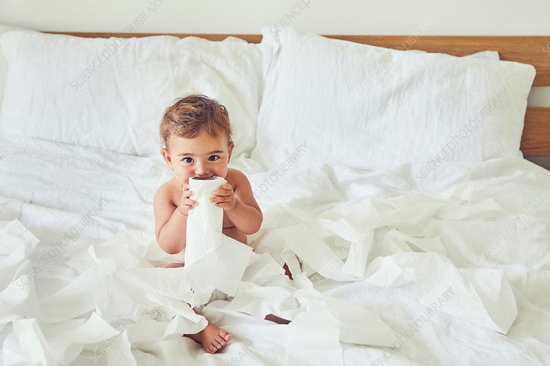 Toddler sitting on bed, holding unravelled toilet roll