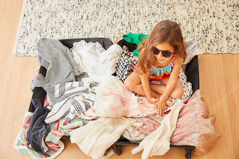 Young girl sitting in suitcase full of clothes