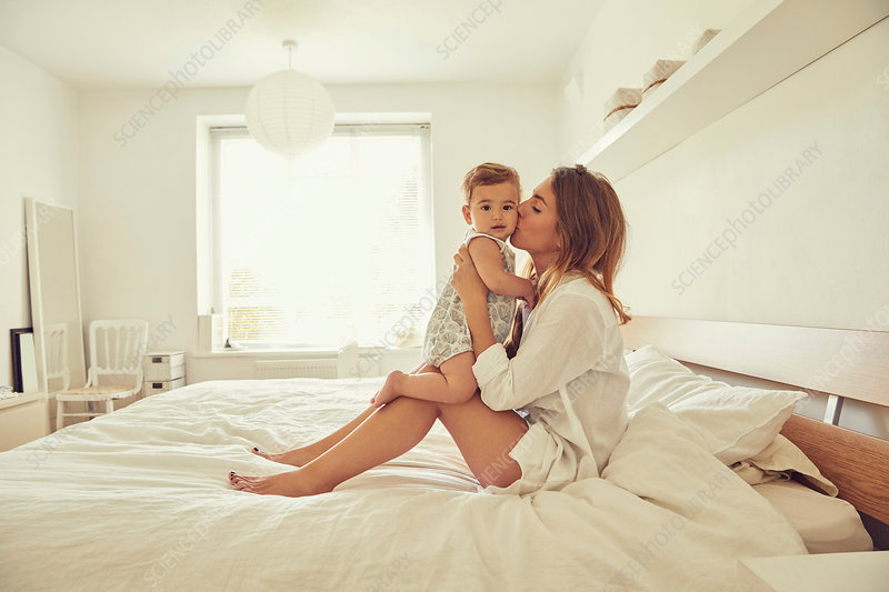 Mother sitting on bed, hugging toddler
