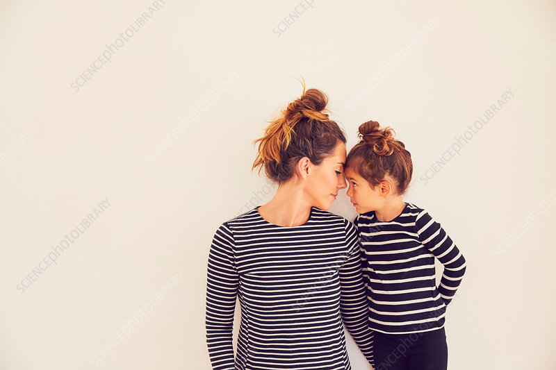 Portrait of mother and daughter, face to face