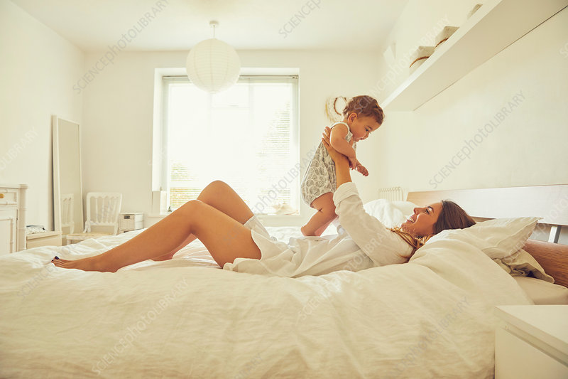 Mother lying on bed, holding toddler up, smiling