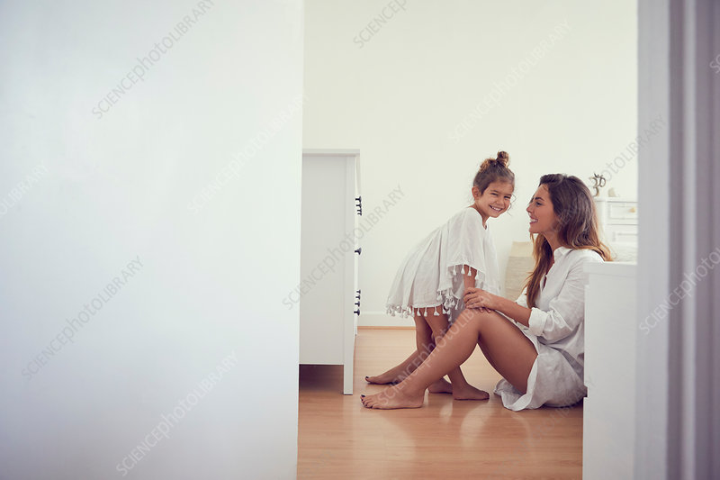 Young girl standing beside mother in bedroom, laughing
