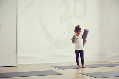 Young girl standing in yoga studio, holding yoga mat