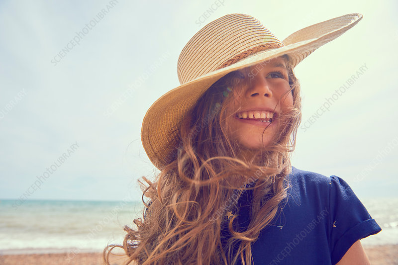 Portrait of young girl on beach, smiling