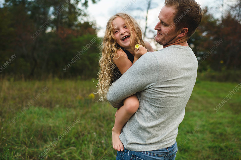 Father and daughter enjoying outdoors on green grassy field