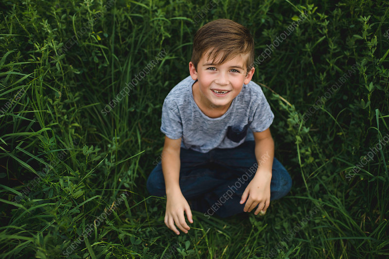 Boy looking up at camera on green grassy field