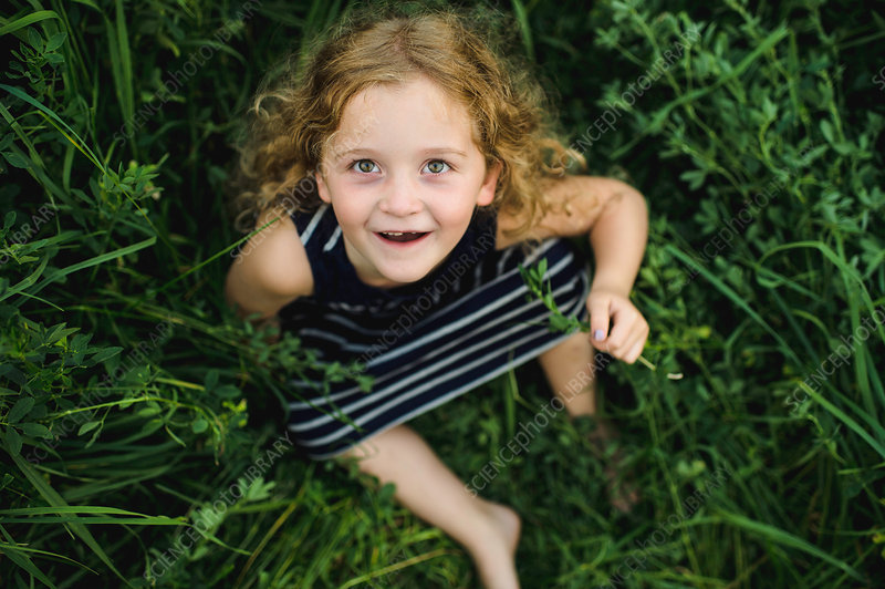 Girl looking up at camera on green grassy field